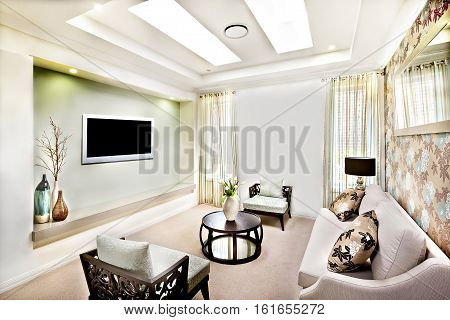 This luxury living room has a long white sofa with pillows close to flower paint decoration on the wall There are two wooden chairs with pillows near a round table with ornamental items close to the television