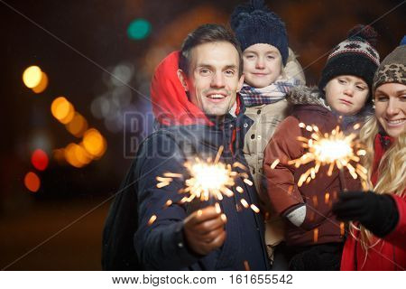 Smiling family with bengal lights in park at night in new year