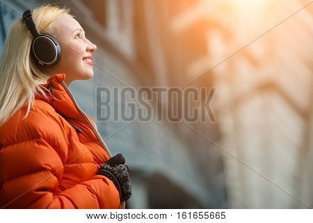 Ginger in orange jacket listening music on headphones indoors