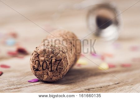 the number 2017, as the new year, written in the cork of a bottle of champagne, on a wooden table full of confetti