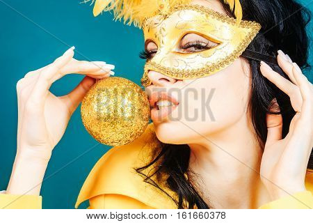 Pretty girl or beautiful woman cute fashion sexy brunette model in festive carnival mask with feathers kisses golden Christmas bauble or ball on blue wall