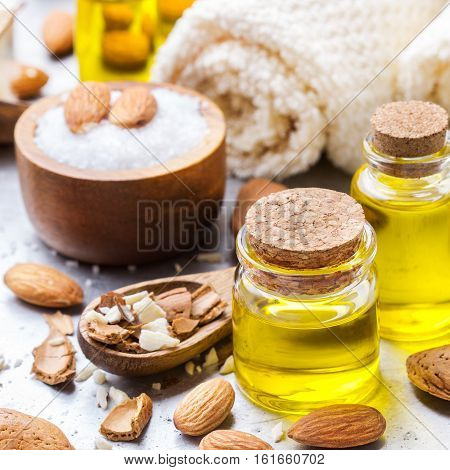 Healthy lifestyle concept. Natural sweet almond essential oil, essence in glass bottle with sea salt on a rustic table for beauty, spa, therapy, bath