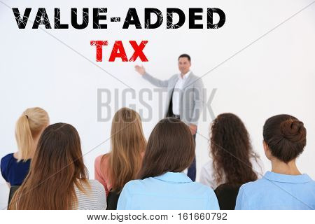 Tax concept. Business people at conference. Text VALUE-ADDED TAX on background
