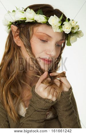 A portrait of a beautiful woman with wreath of roses and elfs ears playing with her long hair.