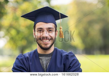 education, graduation and people concept - close up of happy student in mortar boards and bachelor gown outdoors