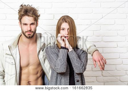 Young couple of handsome man or muscular macho in unzipped jacket with pretty cute girl or beautiful woman in knitted coat on white brick background poster