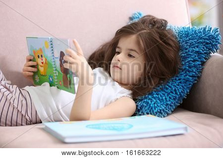 Funny little girl reading book while lying on sofa at home