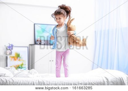 Cute little girl jumping on bed with cuddly toy