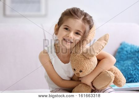 Funny little girl with cuddly toy sitting on sofa at home