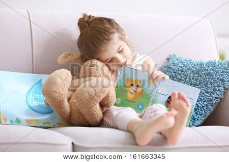 Funny little girl reading book on sofa at home