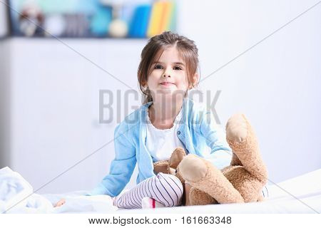 Cute little girl playing with cuddly toy while sitting on bed at home