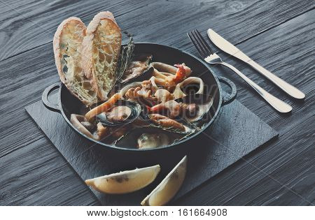 Seafood Stew in Saucepan. Authentic italian restaurant cuisine, healthy delicatessen food. Oysters, shrimps, calamari in white cream sauce with bruschetta. Bowl on dark black wood background, filtered