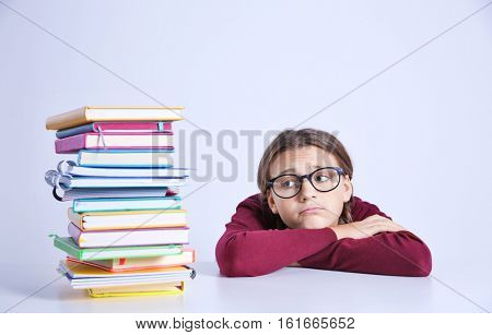 Teenage girl with pile of books sitting at table on white background
