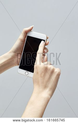 Closeup shot of a woman typing on mobile phone isolated on white background Girl's hand holding a modern smartphone and pointing with figer Blank screen to put it on your own webpage or message.