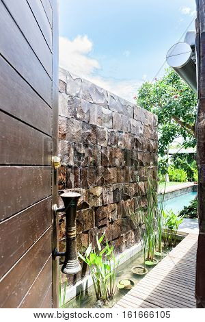 Entrance to a modern water pond from the inside with a brown wooden door and the brass handle attached to it There is a stone water fall with the wet brick wall behind the pond and plants on the vase in the mud near to wooden path next to garden