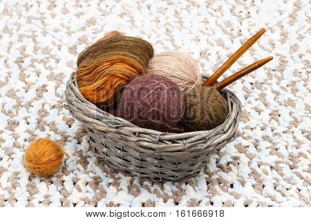 Colorful yarn in balls and coil and wooden needles lies in braided basket near tangle of orange yarn