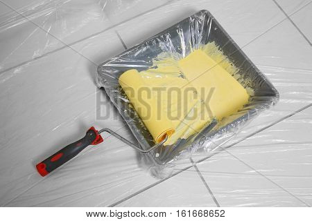 Paint roller and tray on floor covered with polyethylene film