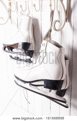 Two pairs of skates hanging on the hook. Family skating concept