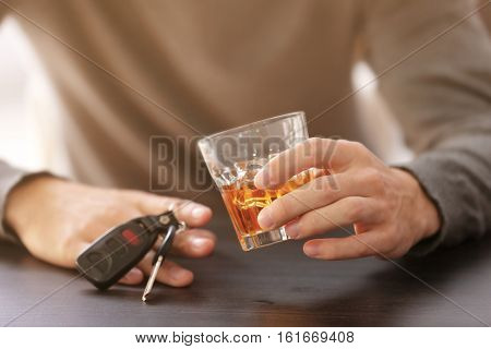 Close up view of man with car key and alcoholic beverage in bar. Don't drink and drive concept