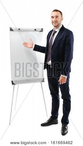 Young businessman standing near flip chart on white background