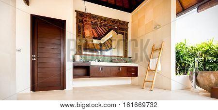 Outdoor washroom with a mirror and cabinets next to a door giving the view of traditional design