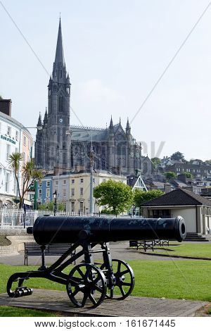 St Colmans Cathedral above cobh town and bay in county cork ireland with canon in foreground