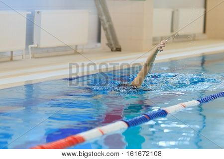 Young Woman In Goggles And Cap Swimming Front Crawl Stroke Style In The Blue Water Indoor Race Pool.
