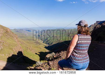 Woman adventurer looks over mountains deep valley dirt road pass landscape summer afternoon.