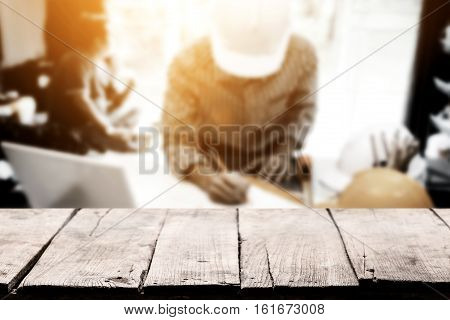 Empty Wooden Tabletop Over Business Engineer Working On His Desk With Chief Engineer Sitting Behind