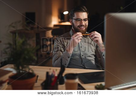 Photo of cheerful bearded web designer dressed in shirt working late at night and looking at computer. Holding pencil.