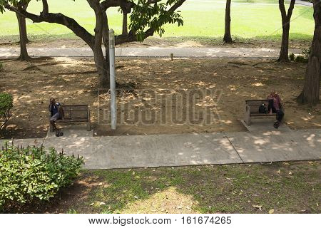 Singapore - 01 November 2014: Alley with two persons plants and bench