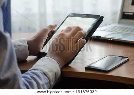Woman in shirt sitting at a table with a tablet. Sitting at a table on a table and cup a smartphone and laptop