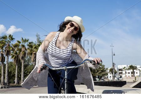 Young happy female in sunglasses and hat on bike enjoying vacation in Lanzarote Gran Canaria.