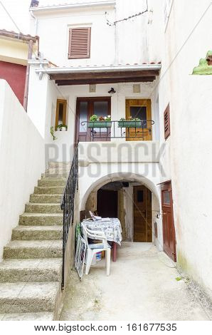 Traditional picturesque Mediterranean architecture at medieval town Vrbnik on Krk island Croatia. View of arched alleys balcony stairs and flowers
