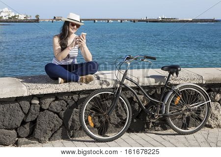 Young smiley woman in hat and sunglasses using device while sitting on quay in Lanzarote Gran Canaria.