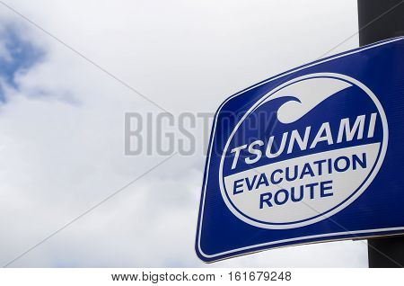 Tsunami Evacuation Route Sign On White Clouds And Blue Sky.