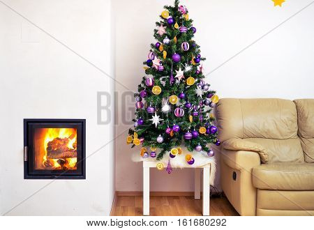 Christmas tree in modern luxury house apartment with fireplace. Sofa next to home decorated Christmas tree with hot fire and flames burning in the fireplace.