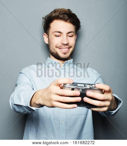 Handsome young man holding camera and making selfie and smiling while standing against grey background