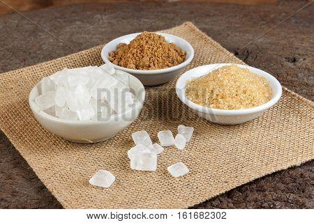 Brown cane sugar and granulated sugar and rock sugar in a cup on old wood.