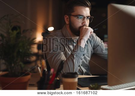 Photo of serious bearded web designer dressed in shirt working late at night and looking at computer. Holding pen.