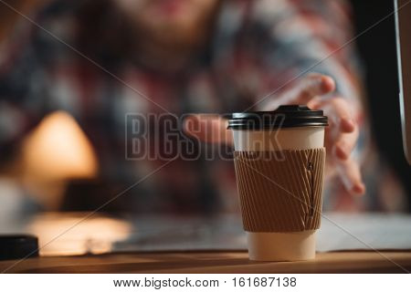 Cropped image of young bearded designer dressed in shirt in a cage working with project late at night and tries to take cup of coffee. Focus on cup of coffee.