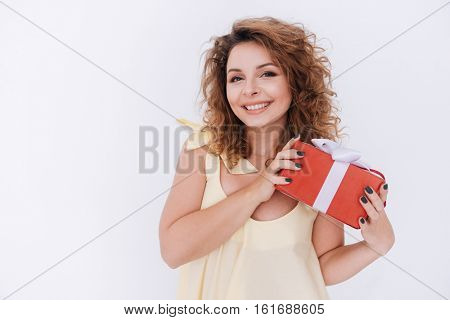 Smiling woman in singlet with gift in hands looking at camera. Isolated gray background
