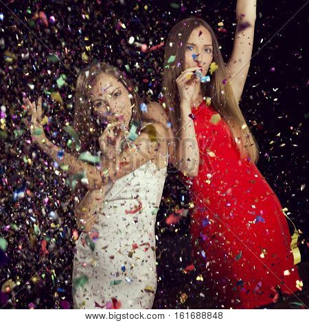 Two beautiful young girls having fun blowing party whistles and dancing at New Year's Eve party