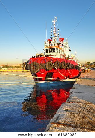 red boat at the new mole of Drapetsona - greek industrial area near to the port of Piraeus