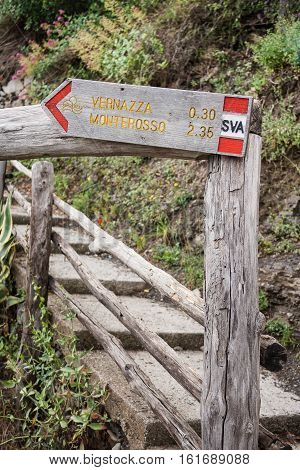 Sign on the Cinque Terre trail showing the distance to Vernazza and Monterosso