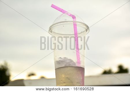 The plastic glass have a little bit water and pink drinking straws under the evening sky.