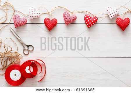 Valentine gift making, diy hobby. Sewed pillow hearts row on red clothespins border with tools for handmade at rustic white wood planks background. Happy lovers day card mockup, copy space