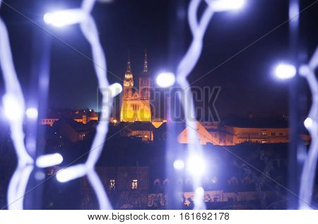 Advent time in city center of Zagreb Croatia. A view of the city and the Zagreb cathedral through illuminating lamps on the upper old town fence.