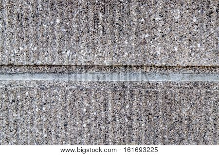 A rugged grey concrete wall with a seperating line