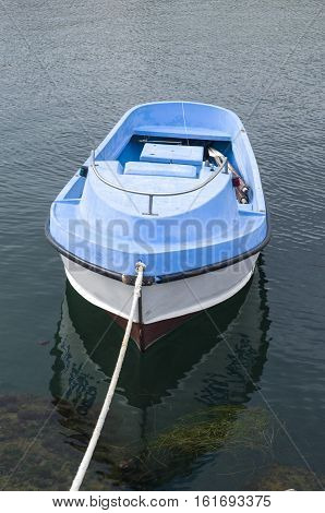 Single small plastic rowing boat in port